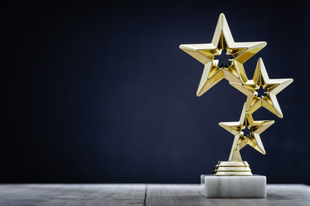 Gold winners award with three stars to be awarded to the first place in a competition or championship standing on a pedestal against a blue background with copy space Foto de archivo