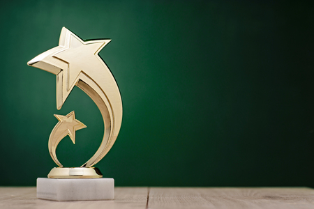 Elegant gold winners trophy with shooting stars to be awarded for the first place in a competition or championship over a dark green background with copy space