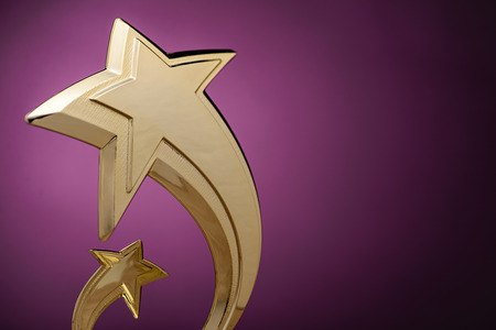 Low angle close up view of two stylish curving gold shooting stars over purple with copy space Stock Photo