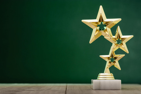 Gold winners award with three stars to be awarded to the first place in a competition or championship standing on a pedestal against a green background with copy space