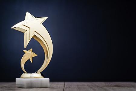 Elegante gouden winnaars trofee met schietsterren die voor de eerste plaats in een competitie of kampioenschap worden toegekend op een donkerblauwe achtergrond met kopie ruimte