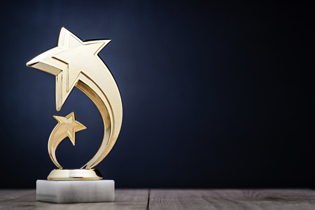 Elegant gold winners trophy with shooting stars to be awarded for the first place in a competition or championship over a dark blue background with copy space Foto de archivo