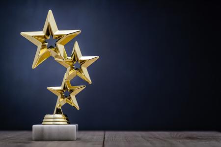 primer lugar: premios ganadores del oro con tres estrellas que se otorgará al primer lugar en una competición o campeonato de pie sobre un pedestal contra un fondo azul con el espacio de la copia Foto de archivo