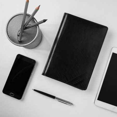 Top view of an office desk with stationery items and electronic gadgets
