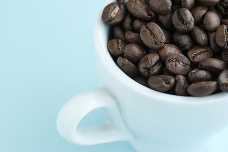 Fried brown coffee beans in a white cup. Stock Photo