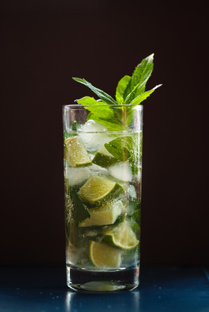Mojito in a glass and lime, ice and green mint.
