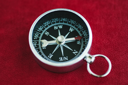 Black traditional compass with arrow on red background