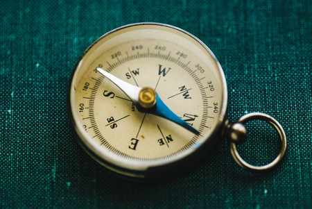 Old yellow retro compass on a green background