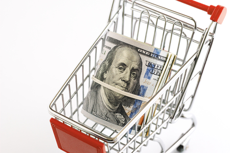 The supermarket cart is filled with American dollars Stock Photo