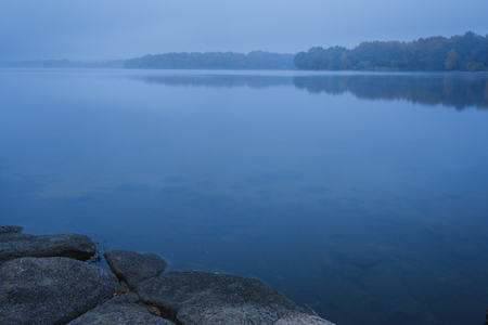 dark blue foggy morning on the lake