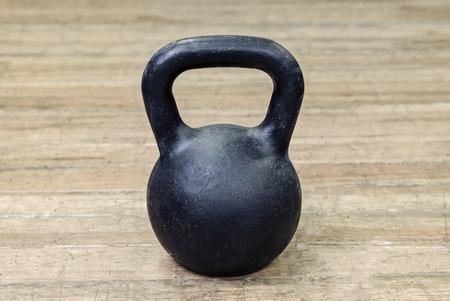 Black heavy kettlebell on wooden floor, sport
