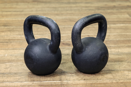 two heavy kettlebell black on wooden background