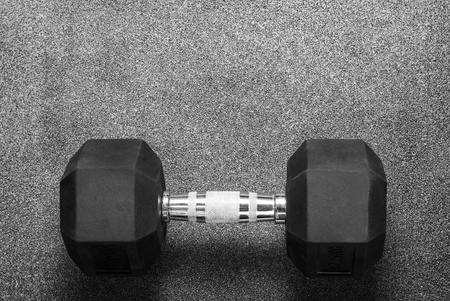 one black dumbbell on a gray background in the gym
