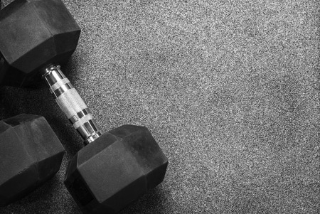 Two black dumbbells on a wooden gray in the gym Stock Photo