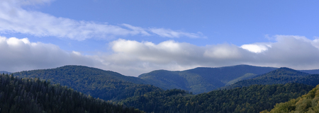 The sky and clouds over the tops of mountains covered with forests