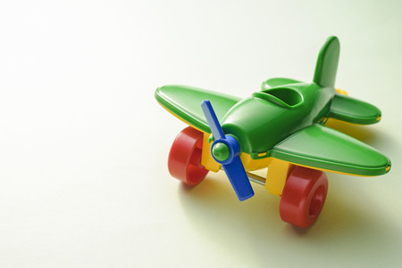 Childrens toy green plane on a gradient green background