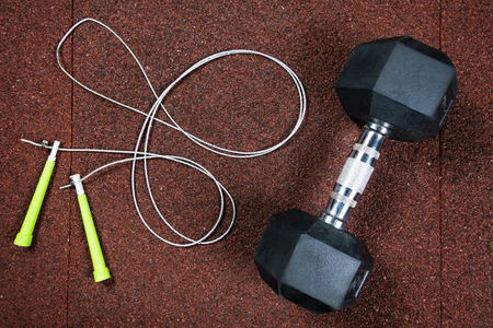 Sports dumbbell and jump rope on a red background in the gym