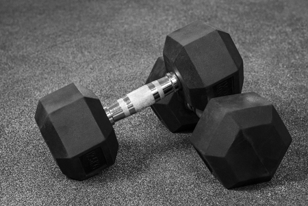 Two black dumbbells on a wooden gray in the gym 免版税图像