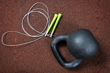 Sports kettlebell and jump rope on a red background in the gym
