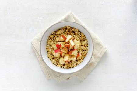 Flat lay view of oatmeal with apple in bowl against white table 版權商用圖片 - 114192418