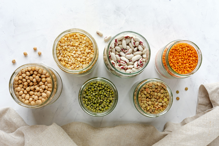 Open glass jars full of assorted dried legumes with mung beans, beans, lentils and peas over a white background
