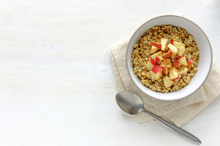 Flat lay view of oatmeal with apple in bowl against white table with copy space