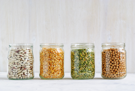Died haricot beans, lentils and chickpeas in glass kitchen jars in a row against a white wall with copy space