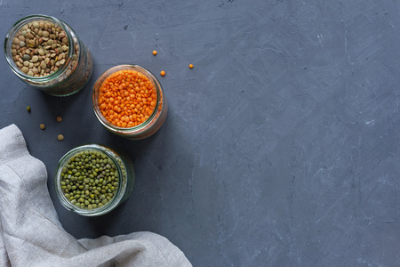 Three jars of lentils and peas over a mottled blue background with copy space viewed from above rich in protein fiber and vitamins