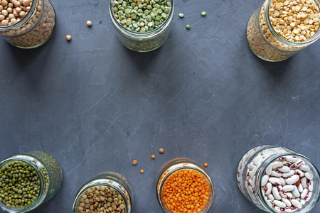 Jars of assorted dried lentils forming a border over a textured blue grey background with copy space