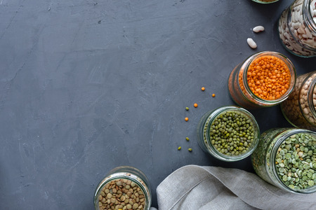 Dried legumes in storage jars on mottled blue background viewed from above with lentils, peas, and beans and copy space