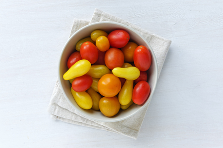 Round white ceramic bowl of red and yellow homegrown tomatoes, on folded white dishcloth. Viewed from above on white wooden background