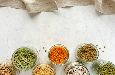 Border of glass jars with pulses and legumes over white viewed from above with copy space for a menu or recipe Stock Photo