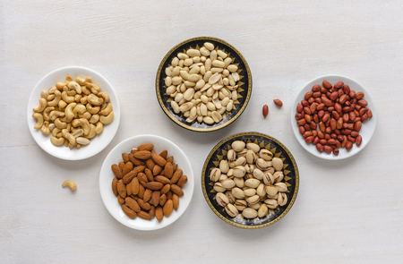 Corner border of an assorted variety of fresh nuts in individual bowls viewed from above
