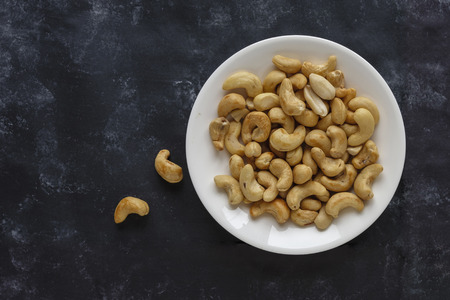 Roasted salted cashew nuts on a white plate viewed from above on a black background with copy space Stock Photo