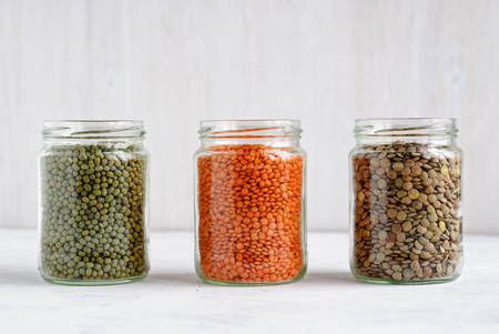 Dried Mung beans, and green and red lentils in glass storage jars standing in a row on white for healthy vegetarian and vegan cuisine