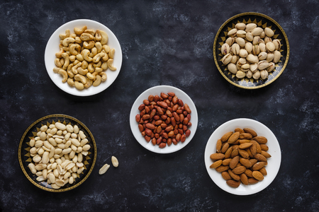 Individual dishes of assorted roasted fresh nuts on a dark background viewed from above with cashews, peanuts, almonds and pistachios Stock Photo