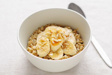 White ceramic bowl of oatmeal with banana slices and honey, served with the spoon on white table background. Viewed from high angle in closeup