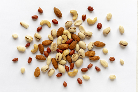Assorted roasted and raw nuts scattered on white with almonds, peanuts, groundnuts, pistachios and cashews viewed in a flat lay still life from above Stock Photo