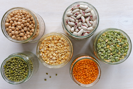 Glass jars filled with assorted dried legumes including red, green and white lentils, peas, haricot beans and mung beans in a healthy diet and nutrition concept