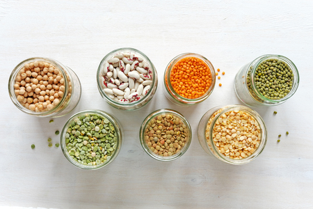 Glass jars full of assorted dried legumes with mung beans, beans, lentils and peas over a white background in a healthy diet Stock Photo