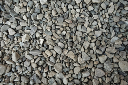Background texture of grey gravel with irregular stones and pebbles viewed from above in a full frame view Stock Photo
