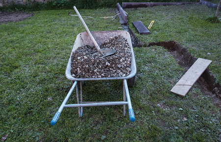 Garden wheelbarrow with two wheels filled with gravel and the shovel, viewed from high angle