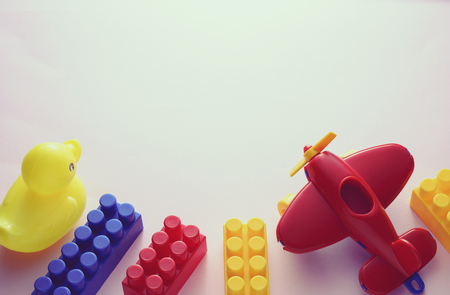 Border of colorful plastic kids toys with building blocks, airplane and duck on white with copy space