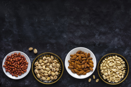 Border with bowls of assorted fresh nuts with peanuts, almonds and pistachios on a dark background with copy space