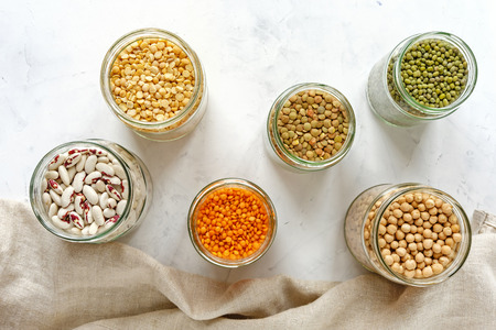 Assorted dried legumes and pulses in glass kitchen jars viewed from above with peas, lentils, beans, chickpeas, on a white cloth Stock Photo