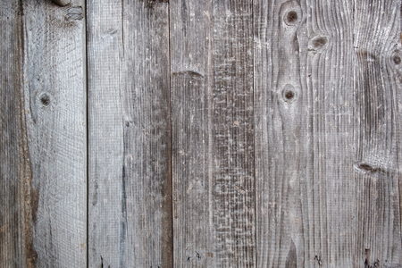 Background texture of old weathered wood planks on an exterior fence or wall in a full frame view Stock Photo