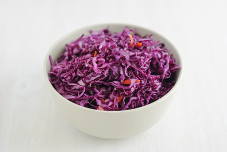 From above shot on ceramic bowl full of tasty purple fermented cabbage on white background Stock Photo