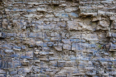 Background texture of irregular layers of rough stone or shale with fractures and cracks