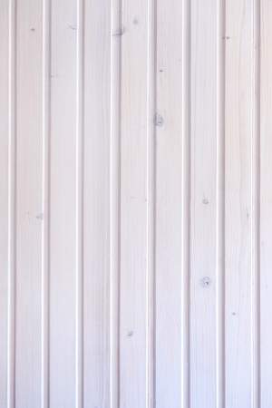 Background texture of a white painted wooden wall with knots and vertical planks in a full frame view Stock Photo