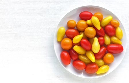 White ceramic plate with yellow and red organic tomatoes, viewed from above on white background with copy space